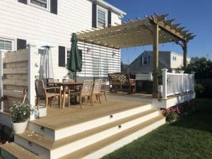 Wooden Sombrero Pergola attached to house covering patio